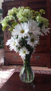white daisies and light green carnations in a vase