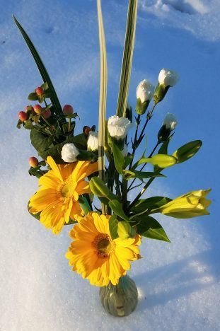 yellow flower bouquet in vase in snow
