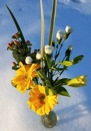 yellow flower bouquet in vase in snow